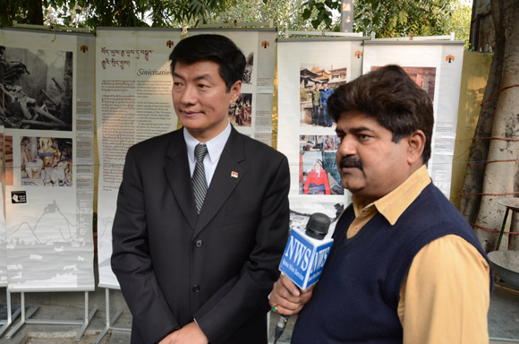 Sikyong Dr Lobsang Sangay in front of exhibit for the Tibetan People's Solidarity Campaign